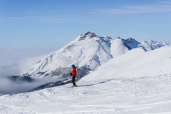 Skier on top of mountain above the clouds. Skier standing on top of a mountain above the clouds stock photo