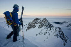 Skier on top of the mountain admiring the sunset. Skier on top of the mountain, over the clouds, admiring the landscape at sunset stock photo