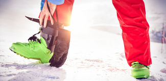 Skier tying his boot strap. Low section of skier tying his boot strap on snow covered field Stock Photos