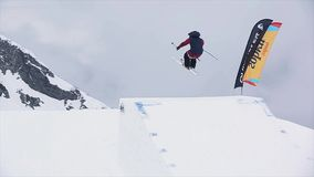 Skier in uniform jump from springboard. Extreme stunt. Snowy mountains. Challenge. Landscape