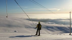 Skier using t bar ski drag lift. At mountain slope stock footage