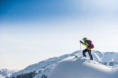 Skier walking on top of the mountain. Royalty Free Stock Photos
