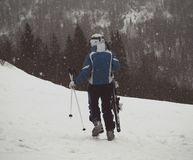 A skier walks down the slope with skis in his hands in the snow Royalty Free Stock Photos