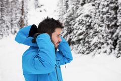 Skier wearing hooded jacket on snowy mountains Stock Image