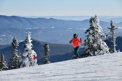 Skier wearing red jacket at sunny day fresh snow. Stowe mountain ski resort