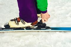 The skier wears footwear for skiing and fixes the fastener. 2019 royalty free stock photos