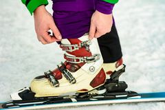 The skier wears footwear for skiing and fixes the fastener. 2019 royalty free stock photo