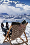 Skier at winter mountains resting on sun-lounger Stock Photo