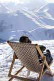 Skier at winter mountains resting on sun-lounger at nice sun day Stock Image