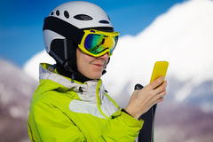 Skier woman look up in smart phone Stock Image
