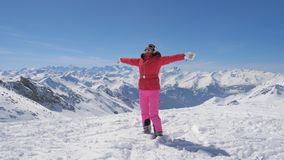 Skier Woman Raises Arms And Turning Then She Falls On Snow Background Mountains