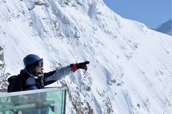 Skier woman in ski clothes and ski googles pointing the directio. Skier woman in ski clothes and ski googles pointing a hill in the mountains Stock Images