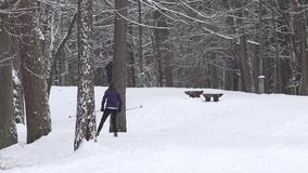 Skier woman skiing on ski trail and runner man in winter park. 4K stock video footage