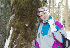 Skier woman standing near the trunk of a tree in winter forest. Beautiful girl in a ski suit leaning against a tree trunk Stock Photography