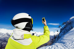 Skier woman taking photos of mountains Royalty Free Stock Image