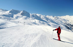 Skieren som tycker om bergsikt på, skidar spåret Royaltyfri Bild