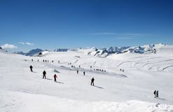 Skiers on Alpine ski slope. Scenic view of group of skiers on Alpine ski slope with blue sky background Royalty Free Stock Photo