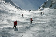 Skiers in the Alps. Skiers on Swiss Alps slopes. Snow blown by the wind gives a misterious feel to the scene Stock Photography