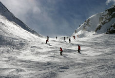 Skiers in the Alps. Skiers on Swiss Alps slopes. Snow blown by the wind gives a mysterious feel to the scene Stock Image