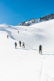Skiers ascending a mountain slope. Stock Photos