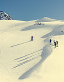 Skiers ascending a mountain slope. Royalty Free Stock Image