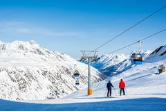Skiers on the background of high snow-capped Alps in sun day, Au Stock Photography