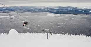 Skiers and Boarders on the Lift. An image of Skiers and Boarders riding the chairlift in a winter wonderland Royalty Free Stock Photos