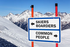 Skiers and boarders versus common people gradation sign. Bifurcating streams against snowy mountain and blue sky winter background stock image