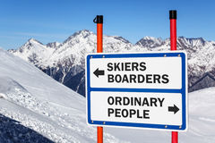 Skiers and boarders versus ordinary people gradation sign. Bifurcating streams against snowy mountain and blue sky winter background stock photos