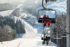 Skiers on cable car in Bukovel with background snow-covered slopes. Skiers on the ski lift riding up at ski resort with beautiful background of snow-covered stock image