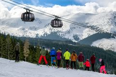 Skiers and cableway at Jasna resort, Slovakia. JASNA, SLOVAKIA - MARCH 22: Skiers and cableway Funitel at ski resort Jasna on March 22, 2019 in Jasna royalty free stock images