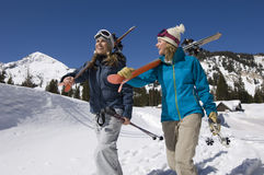 Skiers Carrying Skis on Snowy Landscape Stock Images