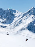Skiers on chair lift in the Alps. The photograph was taken on holiday in the French Alps in Les Deux Alpes Royalty Free Stock Images