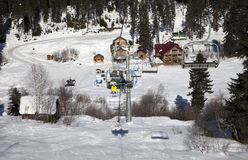 Skiers on chair-lift at ski resort in sun winter day Stock Photo