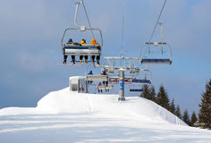 Skiers in chairlift arriving to top of mountain Stock Images