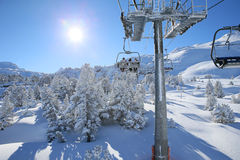 Skiers in the chairlift going on the top of the mountain Royalty Free Stock Images