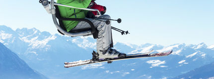 Skiers on chairlift with snowy mountains in the background. Holidays: skiers on chairlift with snowy mountains in the background Stock Photo