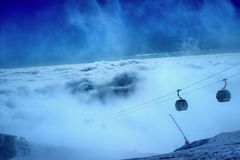 Skiers climb the mountain. Trailers take skiers up the slope of the mountain above the clouds Royalty Free Stock Photography