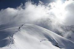 Skiers climbing a snowy mountain Stock Image