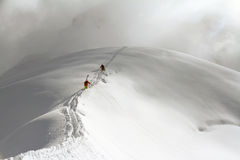 Skiers climbing a snowy mountain royalty free stock photos