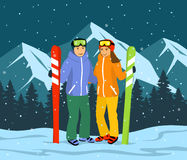 Skiers Couple, man and woman skiing in snow mountains. Evening, Night Scene landscape Royalty Free Stock Photo