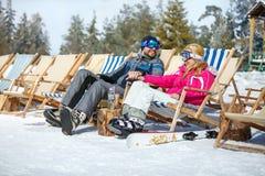 Skiers couple in sun lounger enjoy on sun Royalty Free Stock Photos
