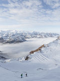 Skiers descend a steep hill. Zell am Cee - December 6, 2014: Skiers descend a steep hill at a ski resort on the glacier Kitssteynhorn and fluffy white clouds at Royalty Free Stock Photography