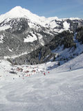 Skiers descend to tiny mountain village Royalty Free Stock Photography