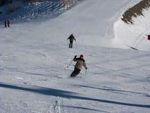 Skiers descending a ski piste Stock Photos