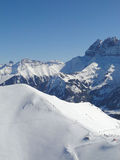 Skiers drop down into the valley Stock Photography
