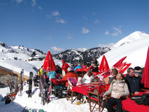 Skiers enjoy the sun during lunch Stock Photo