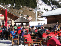 Skiers enjoy their lunch on a sunny day Stock Photos