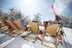 Skiers enjoys in sunbed after skiing, back view. Skiers enjoys in sunbed after skiing on ski terrain, back view Royalty Free Stock Photos