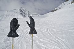 Skiers Gloves at Mountain Top. A skier hangs gloves on ski poles with a massive mountain peak in the distance Royalty Free Stock Image